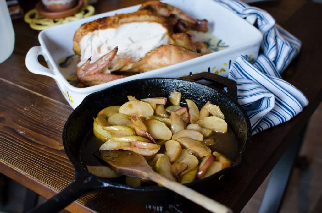 A cooked chicken with fried apples